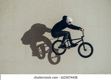 Bmx rider doing a bunny hop with his shadow projected in a stone wall. He is wearing black clothes and white helmet. Black bike. During the sunset.