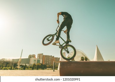 BMX rider doing tricks in the streets.Guy with a bmx bike in the city