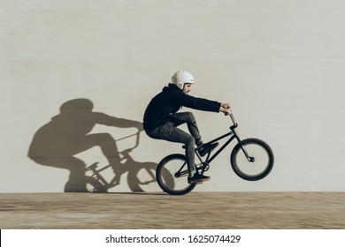 Bmx rider doing a wheelie with his shadow projected in a stone wall. He is wearing black clothes and white helmet. Black bike. During the sunset.