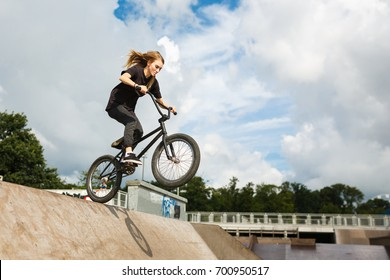 BMX rider is jumping over ramp outdoors