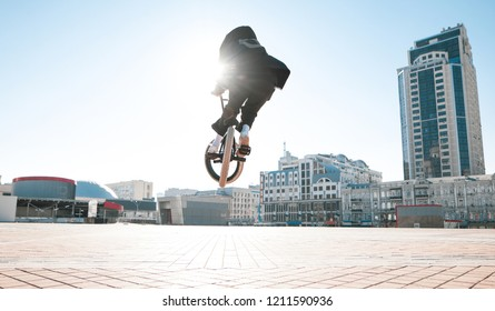 Bmx rider jumps on a bike on a sunny day, against the backdrop of urban scenery.Bmx concept. Street freestyle on bmx