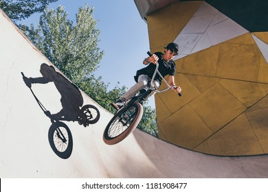 BMX rider makes a TAilwhip trick. Young man doing tricks in the air on a BMX bike. BMX freestyle