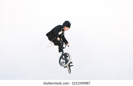 BMX rider makes a TAilwhip trick on a white background. Young man doing tricks in the air on a BMX bike. BMX freestyle