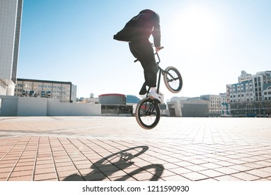 Bmx rider makes a trick in the jump on the street in the background of the city landscape and the sun. Bmx concept. Street freestyle on bmx