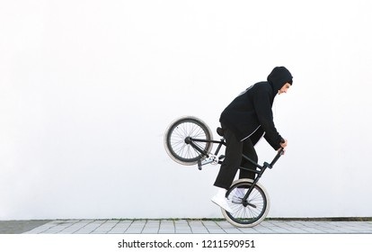 Bmx rider riding on a front wheel of a bicycle on a white background. Copyspace. Bmx freestyle