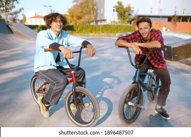 Bmx riders on bikes, training on ramp in skatepark