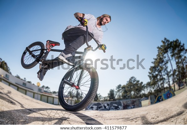 Bmx stunt performed at the top of a mini ramp on a skatepark.