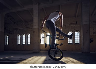BMX stunts in a sunray indoor .