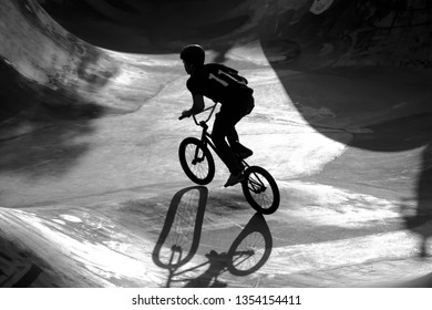 BMX teenage bicycle rider in concrete halfpipe back lighted