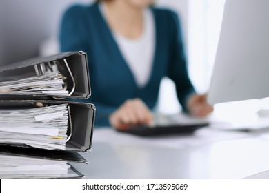 Bnders with papers are waiting to be processed by business woman or bookkeeper working at the desk in office back in blur. Internal Tax and Audit concept