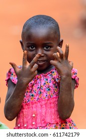 BOABENG, GHANA - JAN 15, 2017: Unidentified Ghanaian little girl in pink dress looks ahead and raises her hands in the local village. Ghana children suffer of poverty due to the bad economy