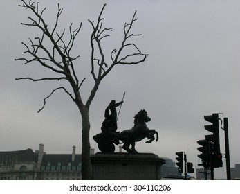Boadicea/Boudica statue London, in silhouette in her chariot and horse with dead tree and traffic lights,, overcast.