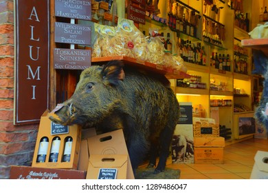 Boar scarecrow in souvenir traditional food and wine shop.  San Gimignano, Toscana / Italy. August 2017: shop with traditional cheese, ham and wine of Toscana
