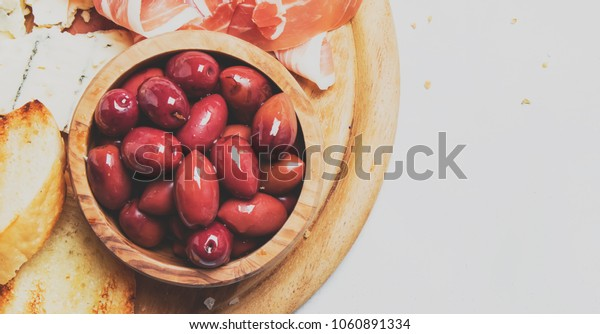 Board with appetizers, crostini, prosciutto, blue cheese and olives, gray background, top view