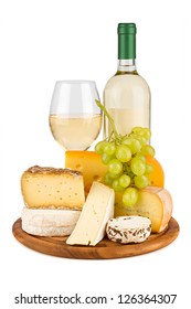 board with cheeses, white wine and grapes.