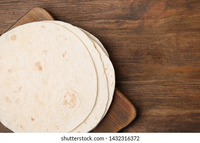 Board with corn tortillas and space for text on wooden background, top view. Unleavened bread