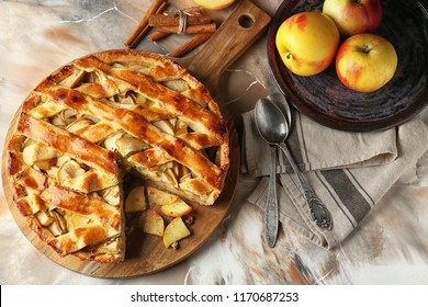 Board with delicious apple pie on table