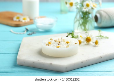 Board with floral candle and chamomile on color wooden table