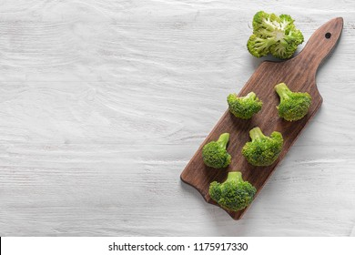 Board with fresh green broccoli on white wooden table