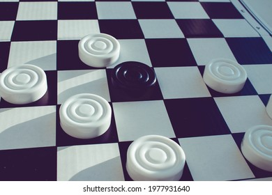 Board game of checkers. Black and white chips for the game. Chess field. Checkers move close-up. Checker in hand.