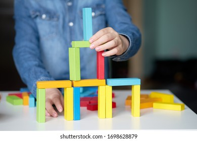 Board game. Child stay home and playing with multi-colored wooden cubes.