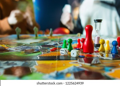 Board game concept- board game field, many figures, meeple, dice, coins and sandglass. Two people play holding cards on blurred background