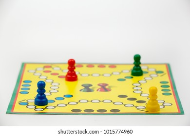 Board game with different colored game pawns on it. Ludo or Sorry board game play figures isolated on white background