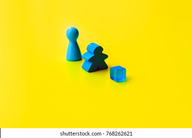 Board game figure, meeple and cube on color background
