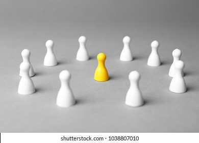 Board game figures and one different on grey background