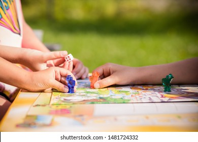 Board game and kids leisure concept. Kids are playing. people holding figures in hand. yellow, blue, green and red wood chips in children play.concept of board games. Dice, chips and cards. Party