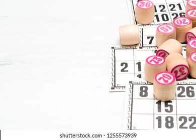 Board game lotto or bingo. Wooden lotto barrels with numbers lying on lotto cards on white desk, with copy space. Vintage game, Russia.