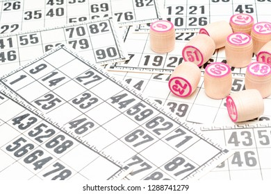 Board game lotto or bingo. Wooden lotto barrels with numbers on background from lotto cards, side view. Vintage game.