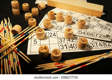 A board game of lotto and mikado are laid out on a black table with cards and barrel. Interesting board games for whole family. Horizontal