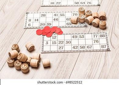 Board game lotto on white desk. Wooden lotto barrels, game cards and red chips for a game in lotto