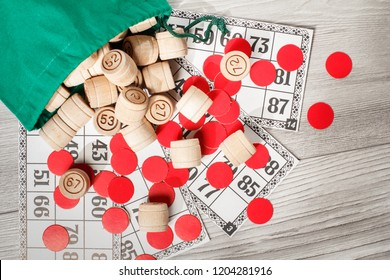 Board game lotto. Wooden lotto barrels with bag, game cards and red chips for a game in lotto. Top view