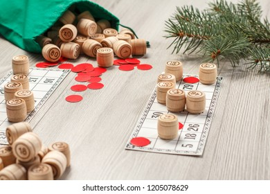 Board game lotto. Wooden lotto barrels with green bag, game cards and red chips for a game in lotto, Christmas fir tree branches on the background. Shallow depth of field