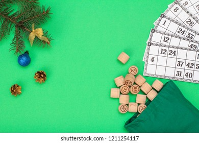 Board game lotto. Wooden lotto barrels with bag and game cards for a game in lotto, Christmas fir tree branches and cones on green background. Top view