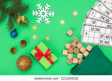 Board game lotto. Wooden lotto barrels with bag and game cards for a game in lotto, Christmas fir tree branches, cones, toy ball and gift box on green background. Top view