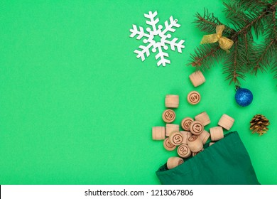 Board game lotto. Wooden lotto barrels with bag for a game in lotto, Christmas fir tree branche and cone on green background. Top view