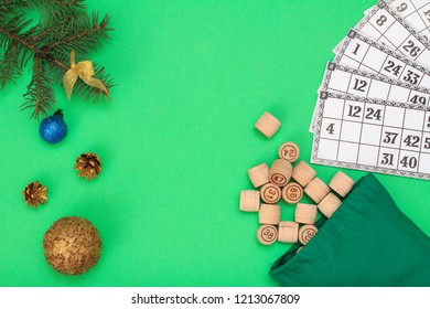 Board game lotto. Wooden lotto barrels with bag and game cards for a game in lotto, Christmas fir tree branche and cones on green background. Top view