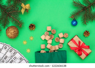 Board game lotto. Wooden lotto barrels with bag and game cards for a game in lotto, Christmas fir tree branches, cones, toy balls, snowflackes and gift box on green background. Top view