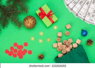 Board game lotto. Wooden lotto barrels with bag, game cards and red chips for a game in lotto, Christmas fir tree branches, cones, toy ball and gift box on green background. Top view