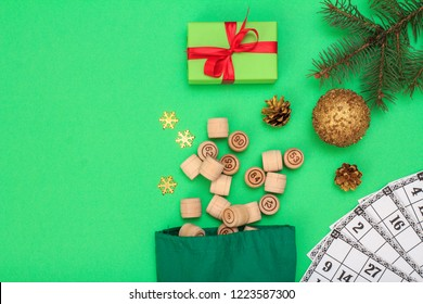 Board game lotto. Wooden lotto barrels with bag and game cards for a game in lotto, Christmas fir tree branch, cones, toy ball and gift box on green background. Top view