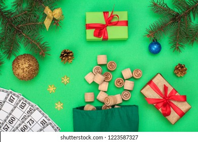 Board game lotto. Wooden lotto barrels with bag and game cards for a game in lotto, Christmas fir tree branches, cones, toy balls and gift box on green background. Top view
