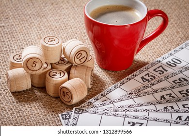 Board game lotto. Wooden lotto barrels and game cards for a game in lotto with cup of coffee on sackcloth.