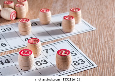 Board game lotto. Wooden lotto barrels and game cards for a game in lotto. Wooden background. Group entertainment, family leisure. Vintage game. Passion and luck.