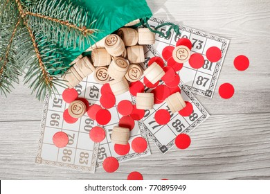 Board game lotto. Wooden lotto barrels with bag, game cards and red chips for a game in lotto, Christmas fir tree branches. Top view