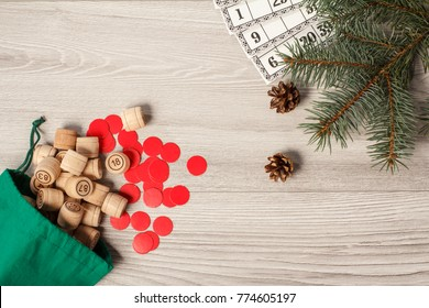 Board game lotto. Wooden lotto barrels with green bag, game cards and red chips for a game in lotto, Christmas fir tree branches and cones. Top view
