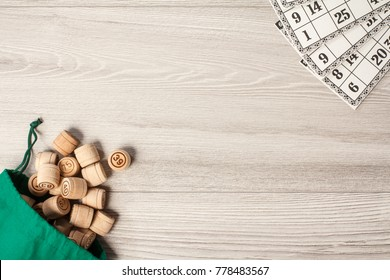 Board game lotto. Wooden lotto barrels with green bag and game cards. Top view