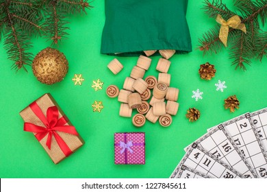 Board game lotto. Wooden kegs with bag and game cards for a game in lotto, Christmas fir tree branches, cones, toy ball, snowflackes and gift boxes on green background. Top view